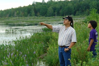 Native American guide Don Chosa points out wild rice beds to his son