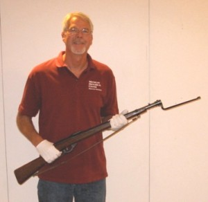 Michigan Historical Museum staff member Steve Ostrander holds a Daisy rifle, with attached bayonet
